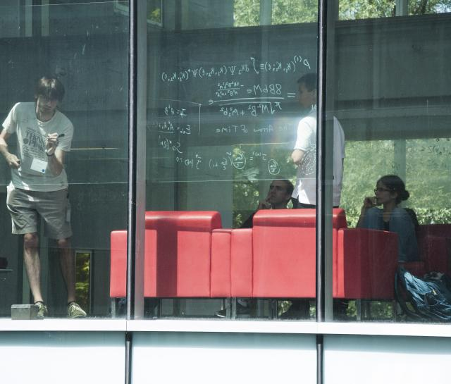researchers interacting behind a window at PI