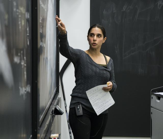 Woman teacher pointing to something on a blackboard