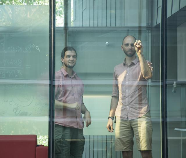 Two men writing equations on a glass wall