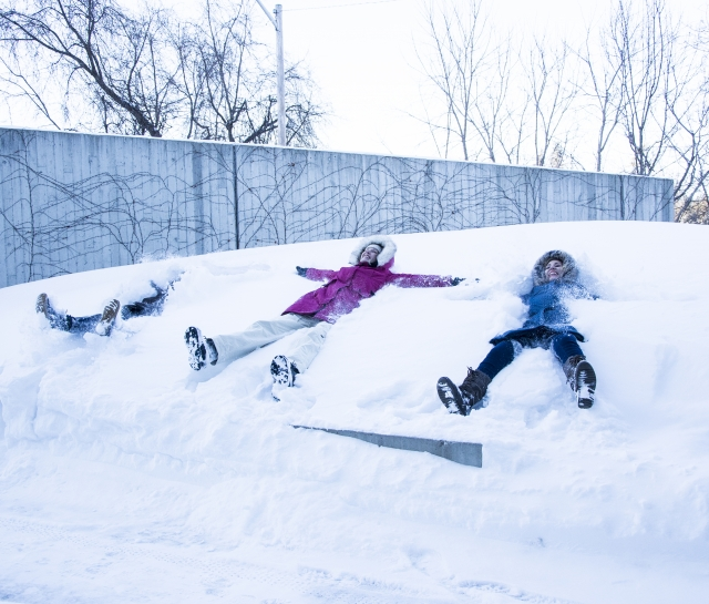students making snow angels in front of the Perimeter Institute building