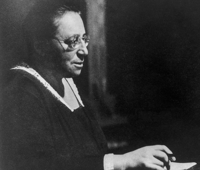 Black and white photo of a woman with glasses in a black cloak