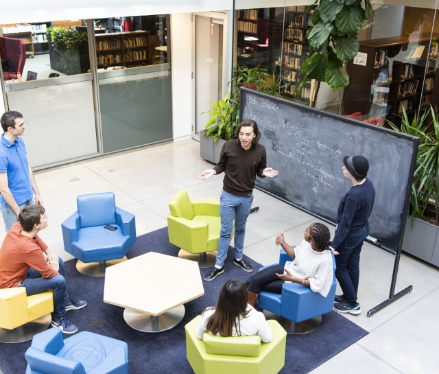 PSI students interacting in front of a blackboard in the atrium