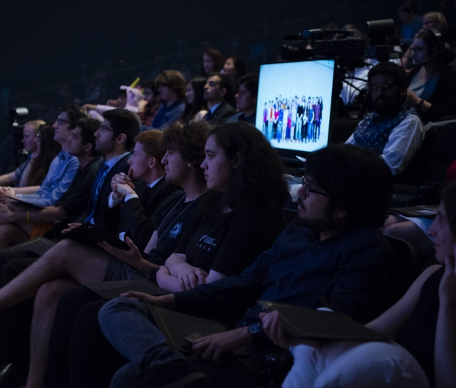 Group of students in a theatre listening to a presentation
