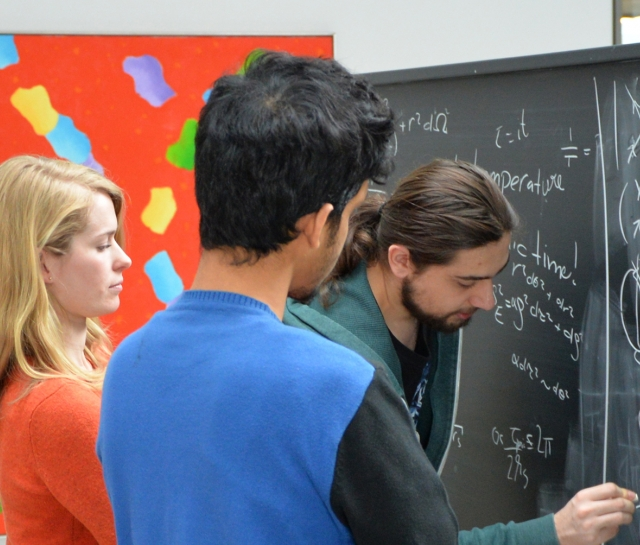 Three men and a woman standing at a chalkboard working on equations