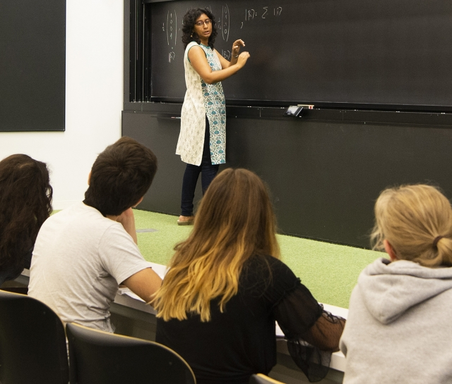 Woman teaching to a group of five students