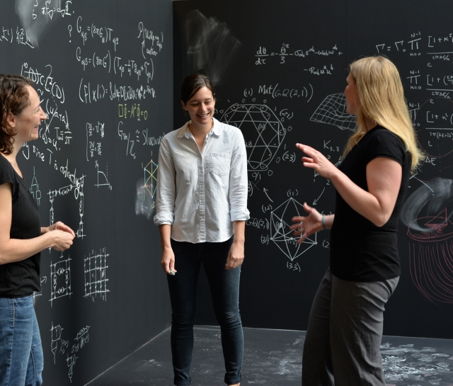 Three women surrounded by chalkboards with equations