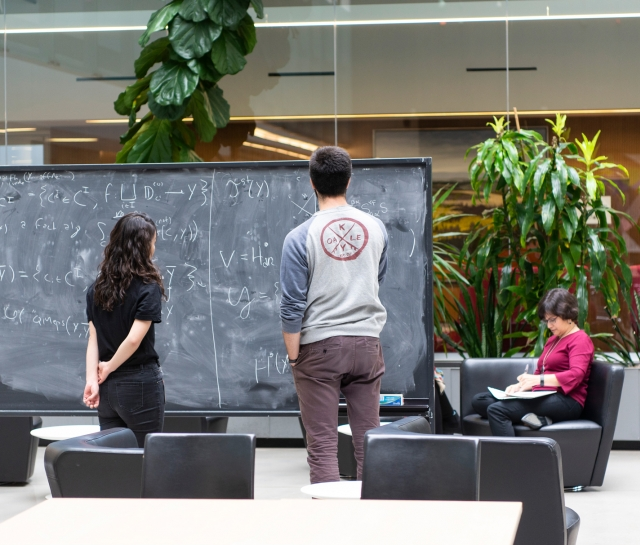 Man and women working at blackboard together in atrium