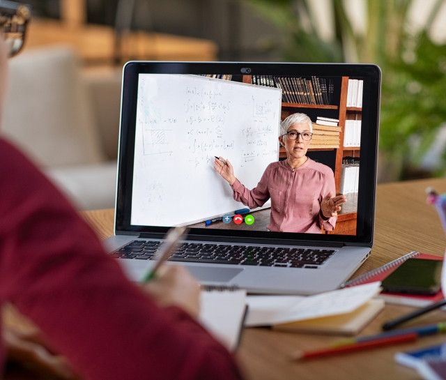 Woman doing a virtual class and teacher on computer screen teaching