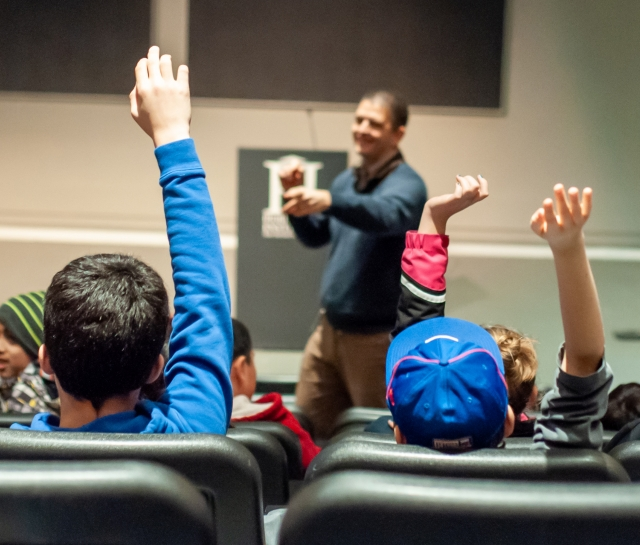 Kids in a lecture hall, raising their hands, asking questions