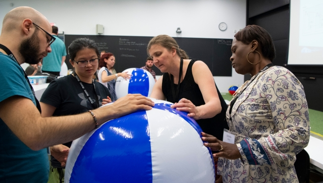 Four teachers working together on an activity with a beach ball