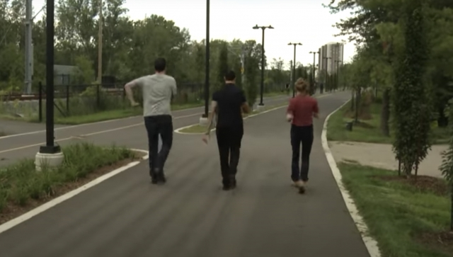 Two men and a woman walking on a path in a park