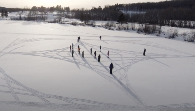 Students making symbols in a field of snow