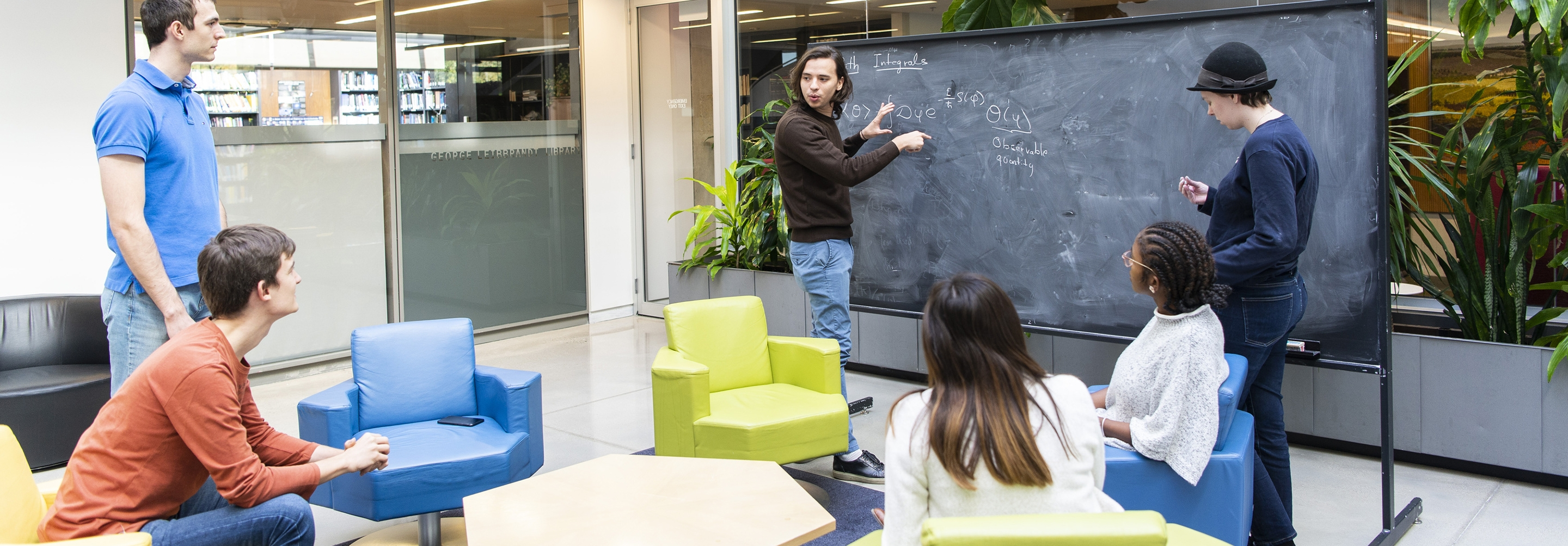 Students talking in a group around a chalkboard
