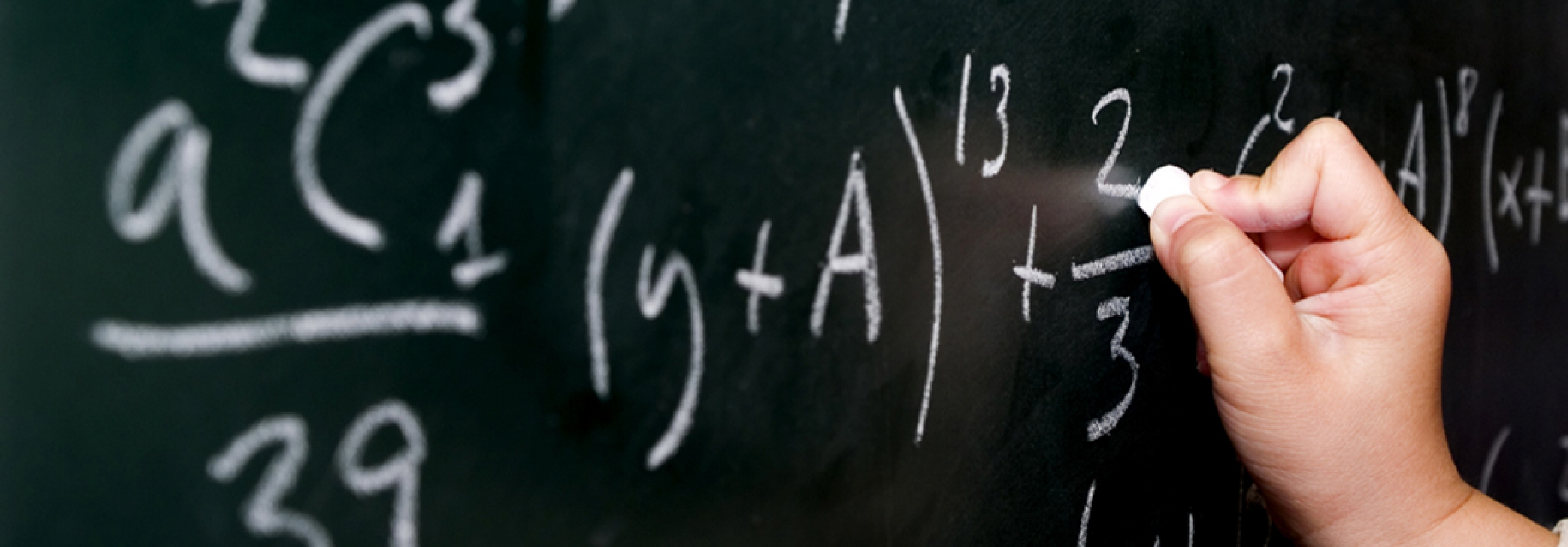 Picture of a hand writing equations on a blackboard
