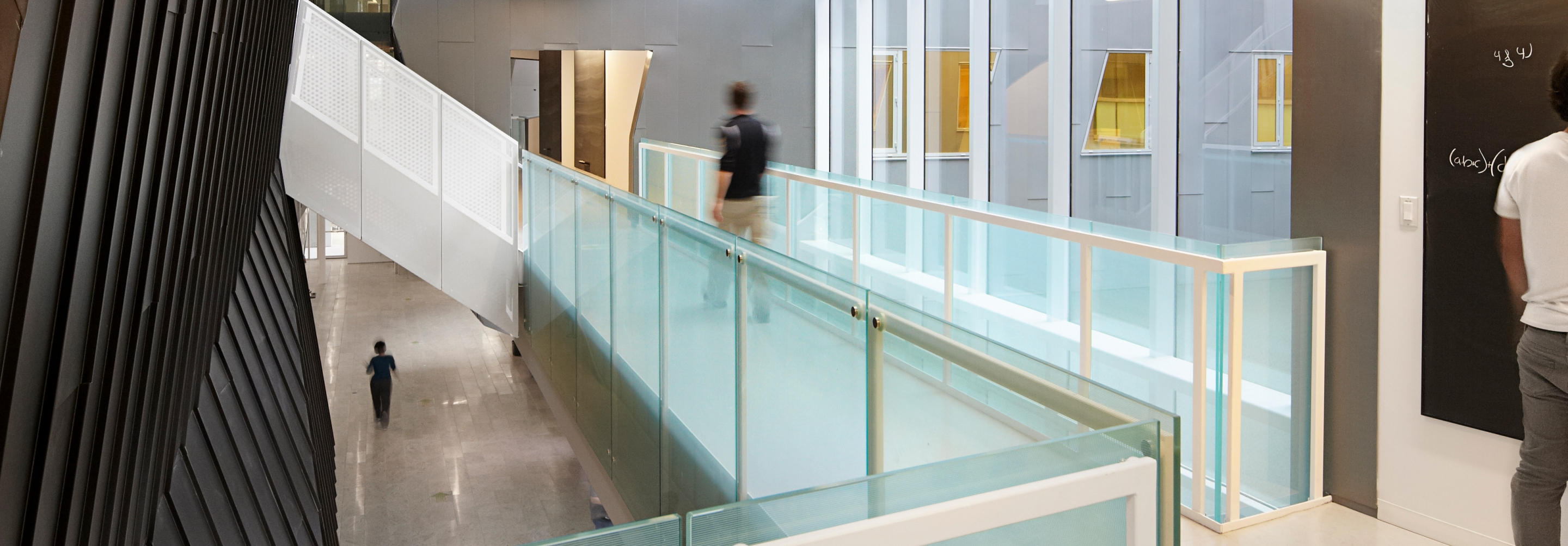 Person walking down an open hallway surrounded by glass windows