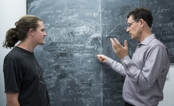 Steffen Gielen and Neil Turok interacting in front of a blackboard covered in equations and graphs