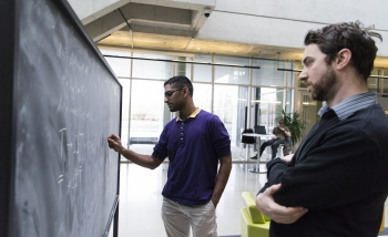 Vasudev Shyam and William Donnelly work together at a blackboard in Perimeter Institute's atrium