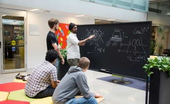 Four men collaborating around a blackboard