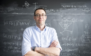 Portrait of a man standing in front of a blackboard of equations